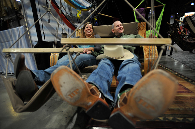 Leah Bowen, left, and Josh Daume relax in an love seat at the Original Air Chair booth during the Cowboy Christmas at the Las Vegas Convention Center on Monday, Dec. 8, 2014, in Las Vegas.   The a ...