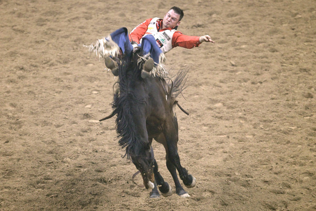 Steven Peebles from Redmond, Ore. rides Flashcard Champion during the bareback riding competition at the first go around at the National Finals Rodeo Thursday, Dec. 4, 2014 at the Thomas & Mack Ce ...