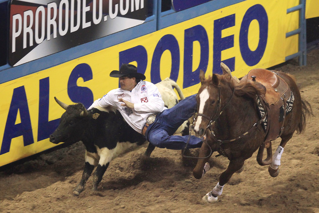Trevor Knowles from Mt. Vernon, Ore. leaps off his horse during the steer wrestling competition at the first go around at the National Finals Rodeo Thursday, Dec. 4, 2014 at the Thomas & Mack Cent ...
