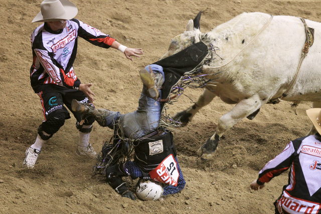 Trey Benton III from Rock Island, Texas hits the ground after being thrown by Cowboy Cool during the first go around at the National Finals Rodeo Thursday, Dec. 4, 2014 at the Thomas & Mack Center ...