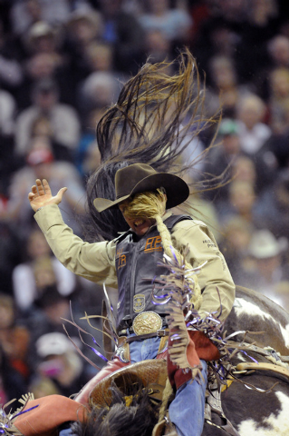 Saddle bronc rider Cody Wright of Milford, Utah, takes a wild ride to a second-place score of 86.5 aboard Billings of Rafter G Rodeo during the fourth round of the 2012 National Finals Rodeo. Wrig ...
