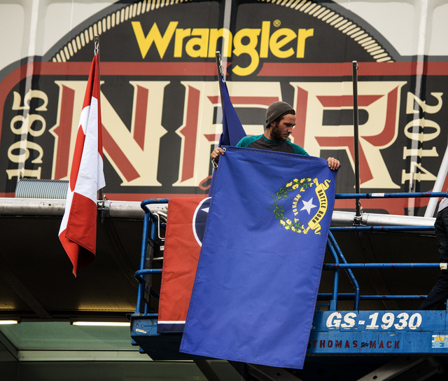 Dylan Shuaib places flags of  contestants  representing states competing in the Wranglers National Finals Rodeo, Monday, Dec. 01, 2014, in front of the Thomas & Mack Arena. This year's NFR has 119 ...