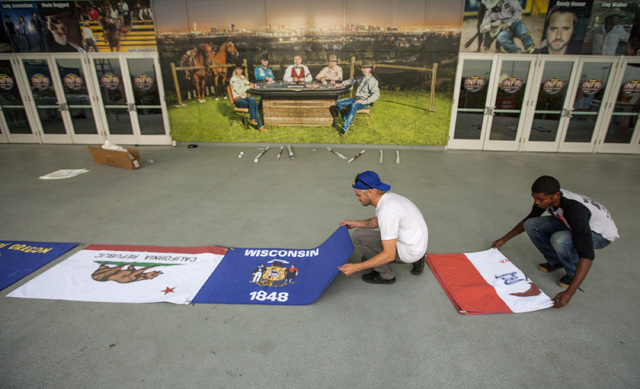 Kyle Jamison, left, and Kelvin Marshall lays out  flags of  contestants representing states competing in the Wranglers National Finals Rodeo,Monday, Dec. 01, 2014, in front of the Thomas & Mack Ar ...