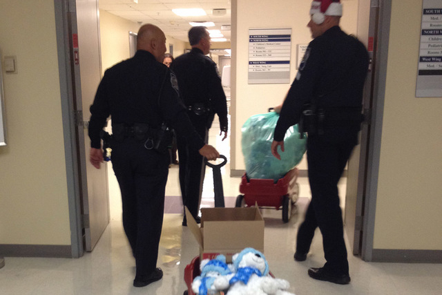 Nevada Highway Patrol troopers deliver teddy bears and toy cars to children at Summerlin Hospital and Medical Center on Wednesday. Troopers visited and gave out toys to 80 children at three Las Ve ...