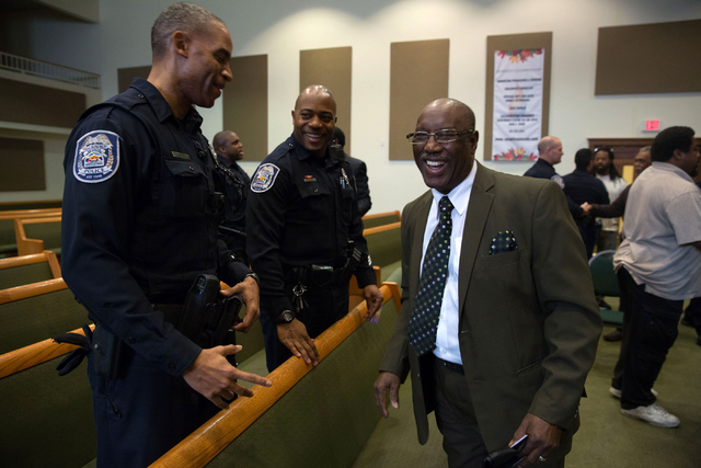 North Las Vegas police officers Selwyn Talley, left, and Michael Harris, center, talk with Rev. S.S. Rogers following a forum discussing policing in minority communities at Ebenezer Church of God  ...
