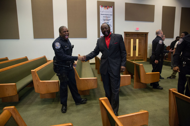 North Las Vegas police officer Aniya Slocum, left, and Rev. Samuel Carroll shake hands following a forum discussing policing in minority communities at Ebenezer Church of God in Christ, located at ...