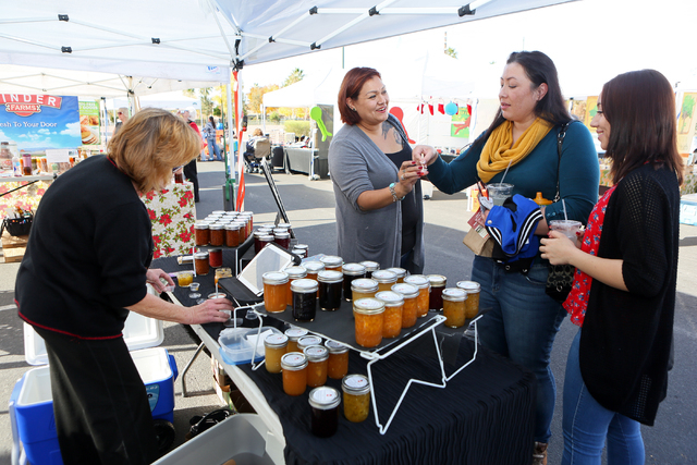 Diana Davis, from left, tends to her booth while Sundance Bravo and Tiffany Magana sample jams at Not Your Grandma's Jams booth at the On the Ranch Farmers and Artisan Market at Craig Ranch Region ...
