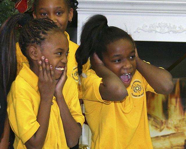 Eight-year-old Lashanerin Edmond, left  and 7-year-old Keyerah Murray react to applause that the choir of the 100 Academy for Excellence received after their performance at the North Las Vegas Chr ...