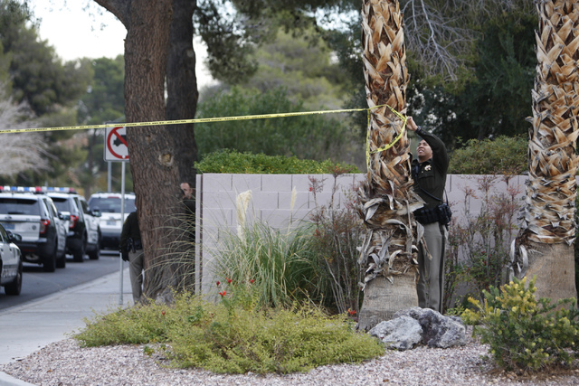 A Las Vegas police officer sets up crime scene tape as they investigate the scene of a reported shooting at the intersection of Tompkins Avenue and Tiburon South Avenue in Las Vegas Sunday, Dec. 2 ...