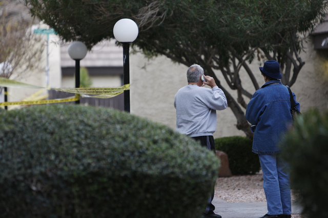 Two unidentified people watch Las Vegas police investigate the scene of a reported shooting at the intersection of Tompkins Avenue and Tiburon South Avenue in Las Vegas Sunday, Dec. 21, 2014. (Eri ...