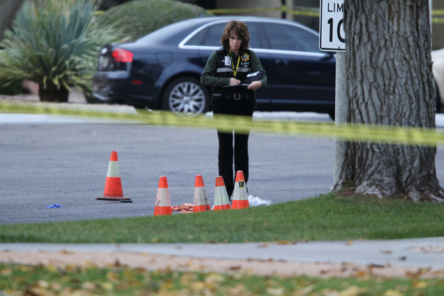A Las Vegas police investigator documents the scene of a reported shooting at the intersection of Tompkins Avenue and Tiburon South Avenue in Las Vegas Sunday, Dec. 21, 2014. (Erik Verduzco/Las Ve ...