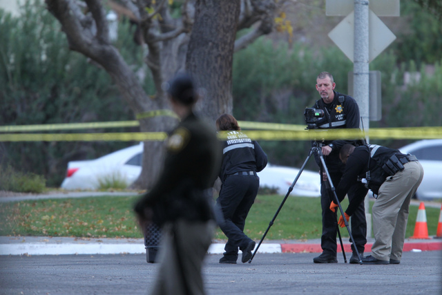 Las Vegas police investigators set up a camera at the scene of a reported shooting at the intersection of Tompkins Avenue and Tiburon South Avenue in Las Vegas Sunday, Dec. 21, 2014. (Erik Verduzc ...