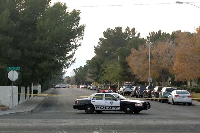 A Metro police car blocks access to a neighborhood after reports of an officer-involved shooting on Sunday in the area of South Mojave Road and East Harmon Avenue. (Kristen DeSilva/Las Vegas Revie ...