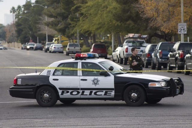 A Metro police officer blocks access to a neighborhood after reports of an officer-involved shooting on Sunday in the area of South Mojave Road and East Harmon Avenue. (Kristen DeSilva/Las Vegas R ...