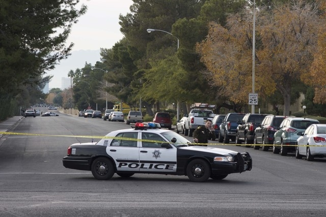 A Metro police officer blocks access to a neighborhood after reports of an officer-involved shooting on Sunday in the area of South Mojave Road and East Harmon Avenue. Police activity can be seen  ...