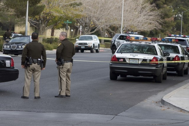 Las Vegas police officers are seen at the site of an officer-involved shooting on Sunday near South Mojave Road and East Harmon Avenue. (Kristen DeSilva/Las Vegas Review-Journal)