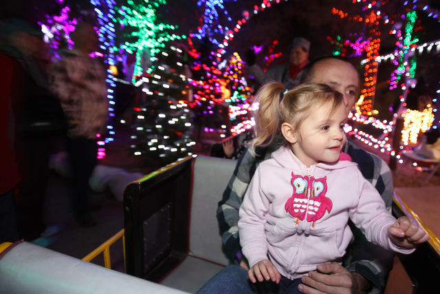 Lyla Cummings, 3, and her father Matthew Cummings of San Diego ride the Forest Express passenger train at Opportunity Village's Magical Forest Nov. 28. Opportunity Village,  6300 W. Oakey Blvd., c ...