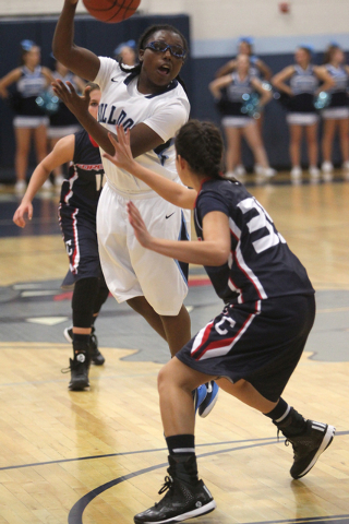 Centennial guard Tanjanae Wells passes over Coronado guard Taylor Tyrell in the second quarter of a basketball game at Centennial High School in Las Vegas on Wednesday, Dec. 3, 2014. Centennial wo ...