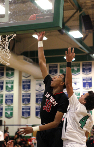Las Vegas forward Tyler Bey (30) shoots in front of Green Valley shooting guard Xavier Jarvis (4) in the first quarter of a prep basketball game at Green Valley High School in Henderson on Tuesday ...