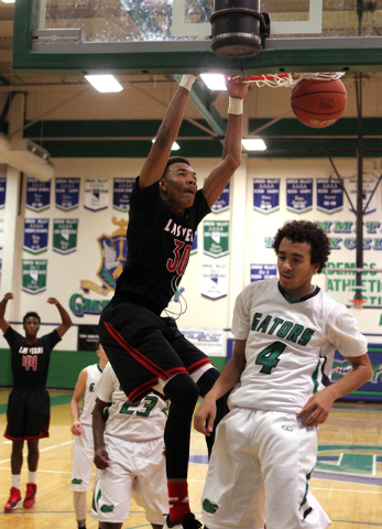 Las Vegas forward Tyler Bey (30) dunks in front of Green Valley shooting guard Xavier Jarvis (4) in the third quarter of a prep basketball game at Green Valley High School in Henderson on Tuesday, ...