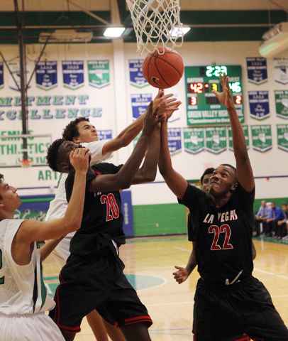 Las Vegas shooting guard Patrick Savoy (22) and Las Vegas guard Dartanion Myers (20) battle for a rebound with  quarter Green Valley shooting guard Xavier Jarvis, left and Green Valley shooting gu ...