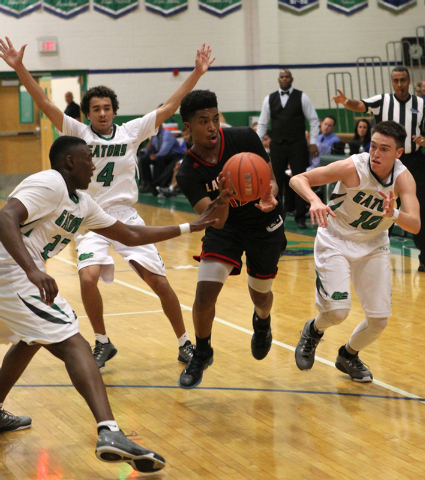 Las Vegas point guard Devon Colley (12) moves the ball against Green Valley forward Romello Jones (23), Green Valley shooting guard Xavier Jarvis (4) and Green Valley shooting guard Brandon Burke  ...