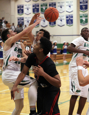 Green Valley shooting guard Brandon Burke (10), Green Valley shooting guard Xavier Jarvis (4) and Las Vegas point guard Devon Colley (12) battle for a rebound in the fourth quarter of a prep baske ...