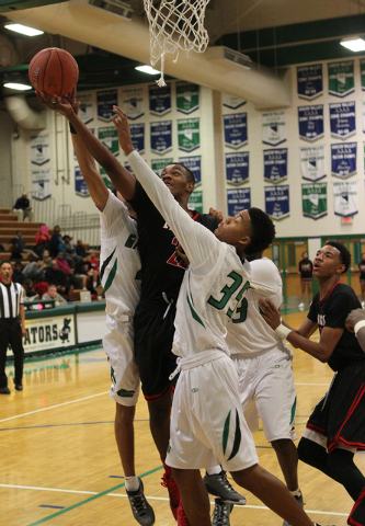 Las Vegas shooting guard Patrick Savoy (22) goes up for a shot between Green Valley shooting guard Xavier Jarvis (4) and Green Valley shooting guard Isiah Macklin (35)  in the first quarter of a p ...