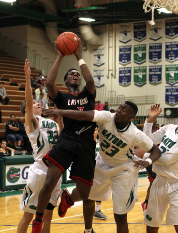 Las Vegas guard Tyshon Raybon (3) shoots between Green Valley shooting guard Dominick Pontoni (22) and Green Valley forward Romello Jones (23) in the second quarter of a prep basketball game at Gr ...