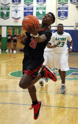 Las Vegas guard Dartanion Myers (20) shoots in front of Green Valley forward Romello Jones (23) in the second quarter of a prep basketball game at Green Valley High School in Henderson on Tuesday, ...