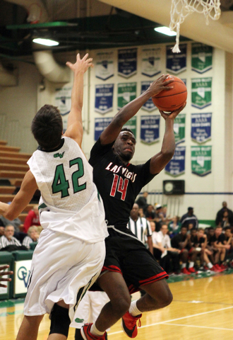Las Vegas guard Deshawn Weathers (14) shoot past Green Valley forward Dylan Trejo (42) in the second quarter of a prep basketball game at Green Valley High School in Henderson on Tuesday, Dec. 9,  ...