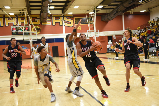 Valley's Cameron Burton (10) drives by Clark's defenders Keyshawn Webb (1) and Ty'Rek Wells (13) during their basketball game played at Clark's home gym in Las Vegas on Saturday, Dec. 12, 2014. (M ...