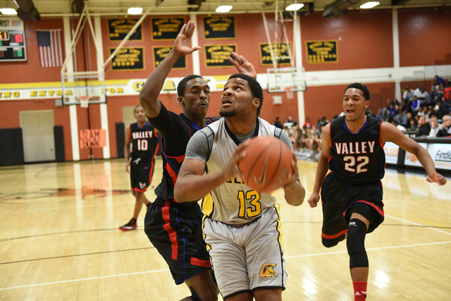 Clark's Ty'Rek Wells (13) goes up for a shot against Valley defenders Nick Brannon (23) and Shea Garland (22) during their basketball game played at Clark's home gym in Las Vegas on Saturday, Dec. ...