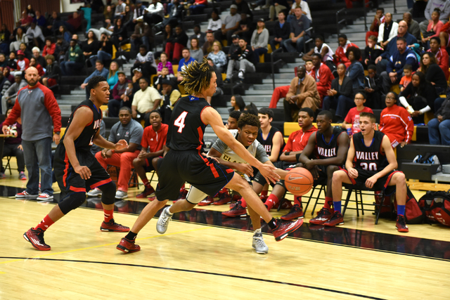 Clark's Keyshawn Webb (1) attempts a pass against Valley defenders from left, Shea Garland (22), and Taveon Jackson (4) during their basketball game played at Clark's home gym in Las Vegas on Satu ...