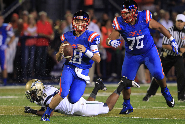 Bishop Gorman quarterback Tate Martell scrambles past St. John Bosco defensive back Bryce Turner during their game Friday. Martell ran for 16 yards and a touchdown and completed 12 of 17 passes fo ...