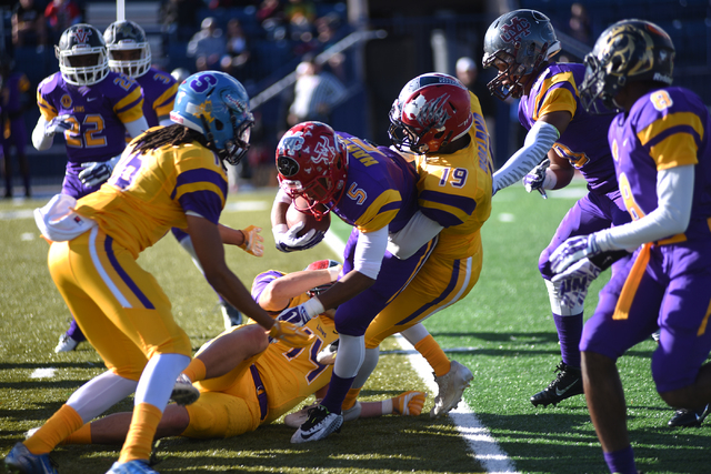 Team Sunset Maurice Harvey (5) is tackled by team Sunrise defender Myles Holland (19) during the 42nd annual West Charleston Lions Club Charity High School All-Star Football game played at the Bis ...
