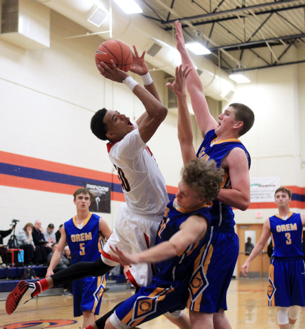 Las Vegas forward Tyler Bey crashes into Orem forward Noah Johnson and center Richard Harward, right, at the Tarkanian Classic on Thursday at Bishop Gorman. Bey had 16 points, seven rebounds and t ...
