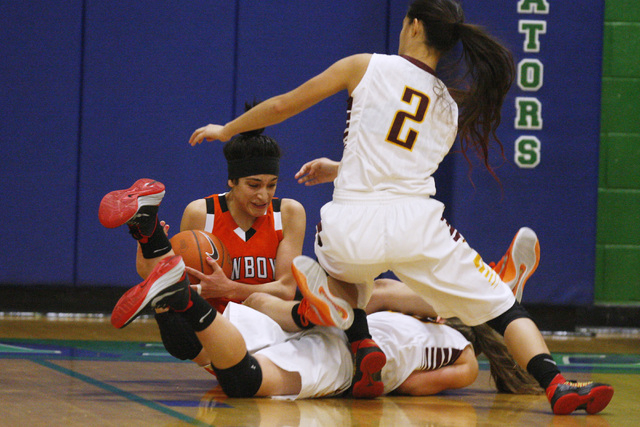 Chaparral guard Abigail Delgado falls over Dimond of Anchorage, Alaska guard Nikki Forrey during their game at the Gator Winter Classic tournament Wednesday, Dec. 31, 2014 at Green Valley High Sch ...