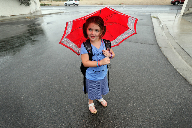 Madison Matthews, 6, walks home in the rain after school on Monday, Sept. 8, 2014.  The first grader was met by her mother and sister at the bus and walked home together. (Photo by David Becker/La ...