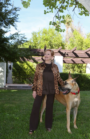 Nancy Houssels stands with her dog named Maureen O'Hara in her backyard Friday, Oct. 10, 2014, in Las Vegas. Houssels lives in Rancho Circle gated community in a home that was built in 1965. (Rond ...