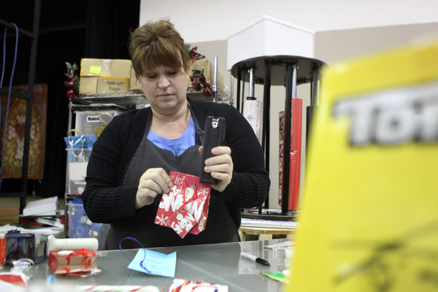 Volunteer Maureen Cerza gift wraps a Christmas gift as part of the Angel Tree program at St. Elizabeth Ann Seton Catholic Church in Las Vegas Sunday, Dec. 14, 2015. The program encourages charity  ...