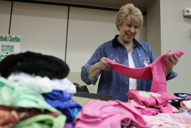 Carmen Esparza assorts through girls clothing waiting to be gift wrapped as part of the Angel Tree program at St. Elizabeth Ann Seton Catholic Church in Las Vegas Sunday, Dec. 14, 2015. The progra ...