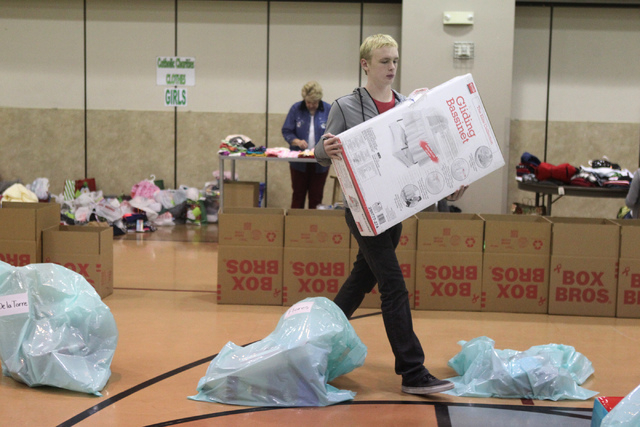Volunteer Spencer Howard, 14, moves a Christmas gift part of the Angel Tree program at St. Elizabeth Ann Seton Catholic Church in Las Vegas Sunday, Dec. 14, 2015. The program encourages charity by ...