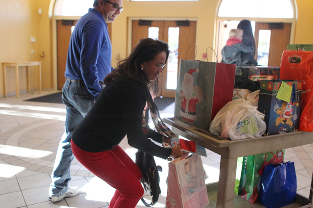 Rosa Litchfield drops off a Christmas gift as part of the Angel Tree program at St. Elizabeth Ann Seton Catholic Church in Las Vegas Sunday, Dec. 14, 2015. The program encourages charity by allowi ...