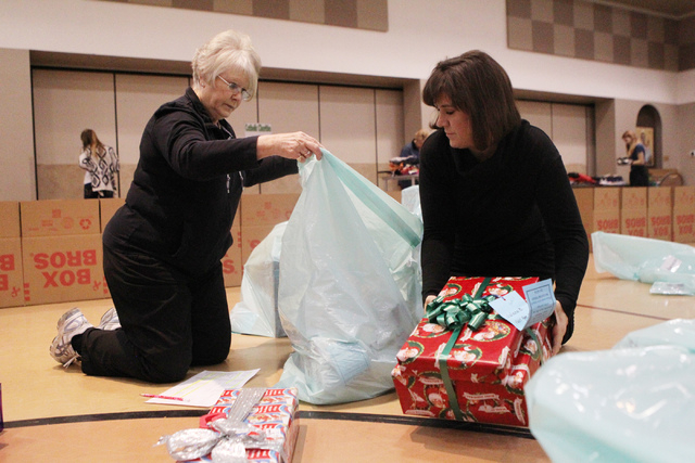 Outreach coordinator Jeanne Kilduff, left, and volunteer Colleen Soucoup, fill a bag with Christmas gifts for a family as part of the Angel Tree program at St. Elizabeth Ann Seton Catholic Church  ...