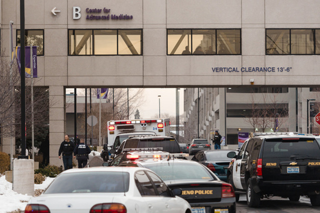 Officers gather in front of the Renown Regional Medical Center after a lone gunman shot and injured four people before killing himself on Tuesday, Dec. 17, 2013 in Reno. (AP Photo/Scott Sady)