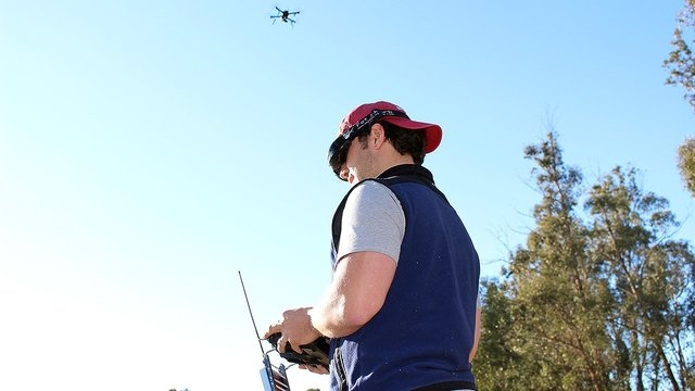 3D Robotics employee Pablo Lema views live video streamed from the drone above his head. The first-person view is displayed on his goggles, while he steers the device with a hand-held controller.  ...