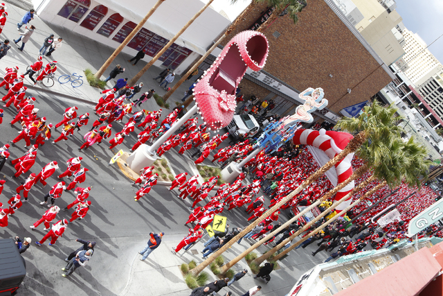 People head out from the start line down Fremont Street during the Great Santa Run in downtown Las Vegas on Saturday, Dec. 7, 2013. (Chase Stevens/Las Vegas Review-Journal)