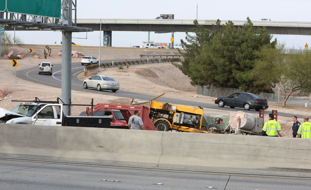 A construction truck driver, left, and Las Vegas police are seen at the accident scene where a crash has blocked all northbound lanes of U.S. Highway 95 at the Spaghetti Bowl Friday, Dec. 5, 2014. ...