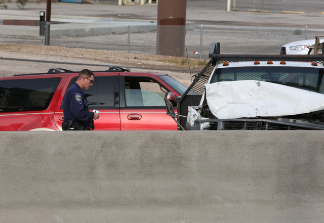A Las Vegas police investigates the accident scene where a crash has blocked all northbound lanes of U.S. Highway 95 at the Spaghetti Bowl Friday, Dec. 5, 2014. Nevada Highway Patrol responded abo ...